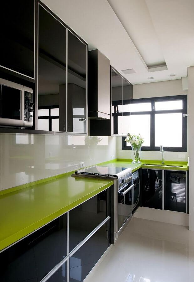 Cozinha preta e branca decorada com bancada na cor verde limão