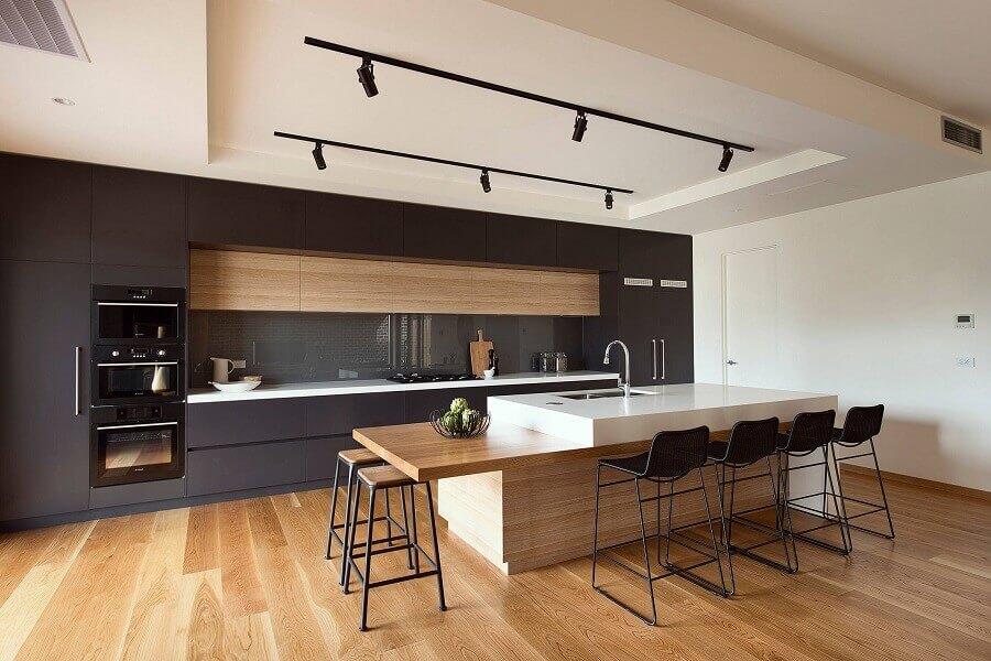 cozinha preta grande decorada com ilha gourmet planejada com bancada de madeira Foto HappyModern