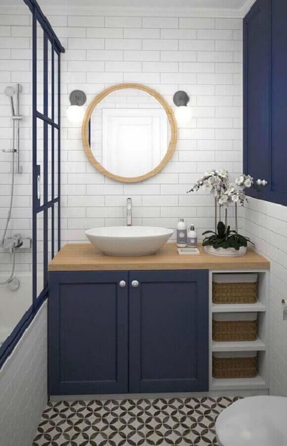 Decoração azul e branco com armário de banheiro planejado pequeno com bancada de madeira