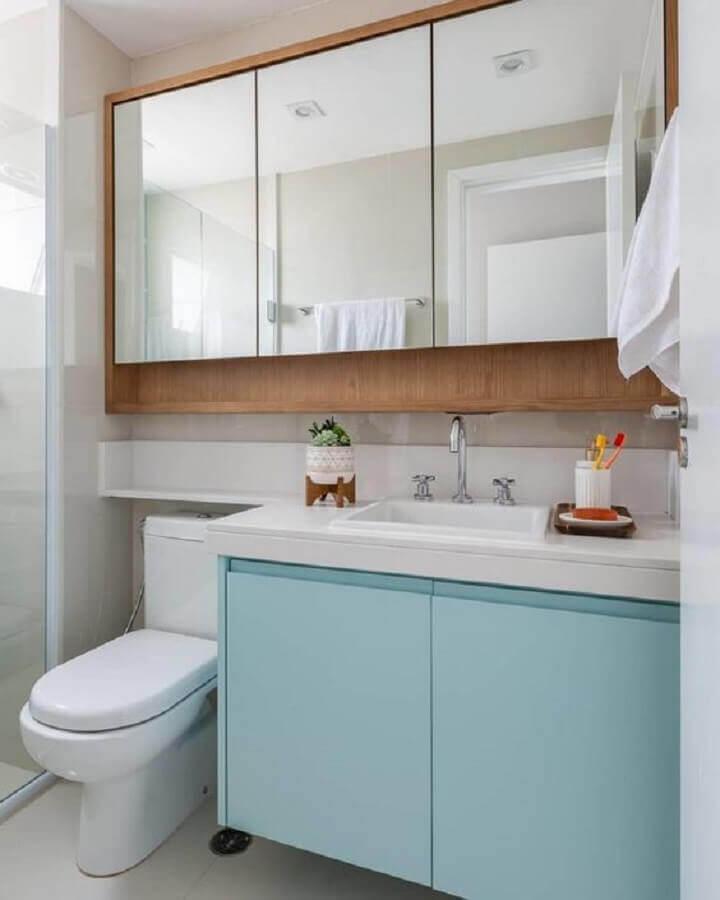 Decoração com gabinete azul pastel e espelheira para banheiro de madeira