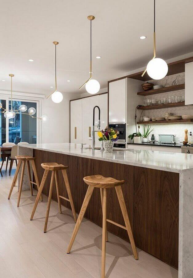 Decoração com luminária pendente moderna e banquetas para bancada de madeira