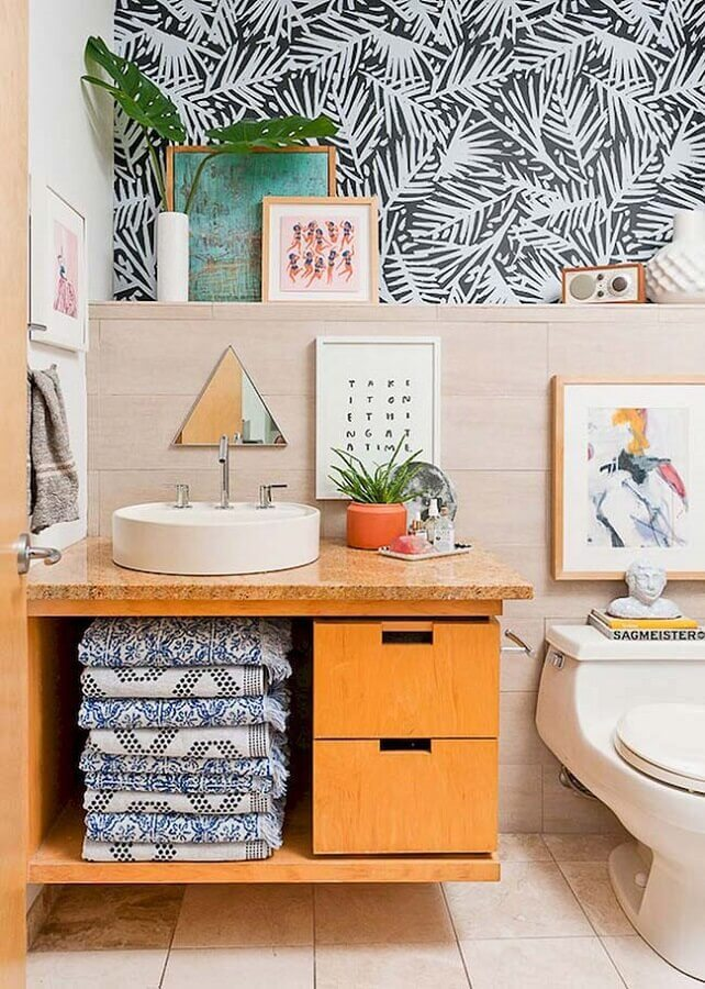 Decoração com papel de parede e armário de banheiro pequeno com cuba redonda