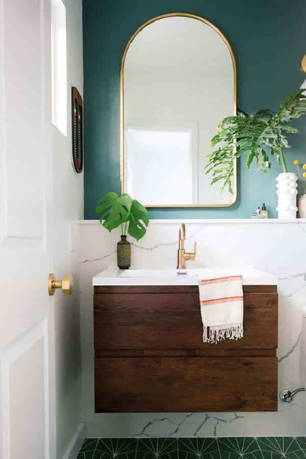 Decoração com parede verde e armário pequeno de banheiro de madeira