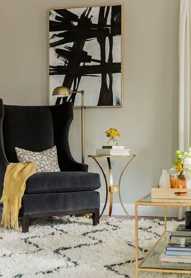 Decoração com poltrona preta para sala clássica com móveis de vidro com detalhe dourado