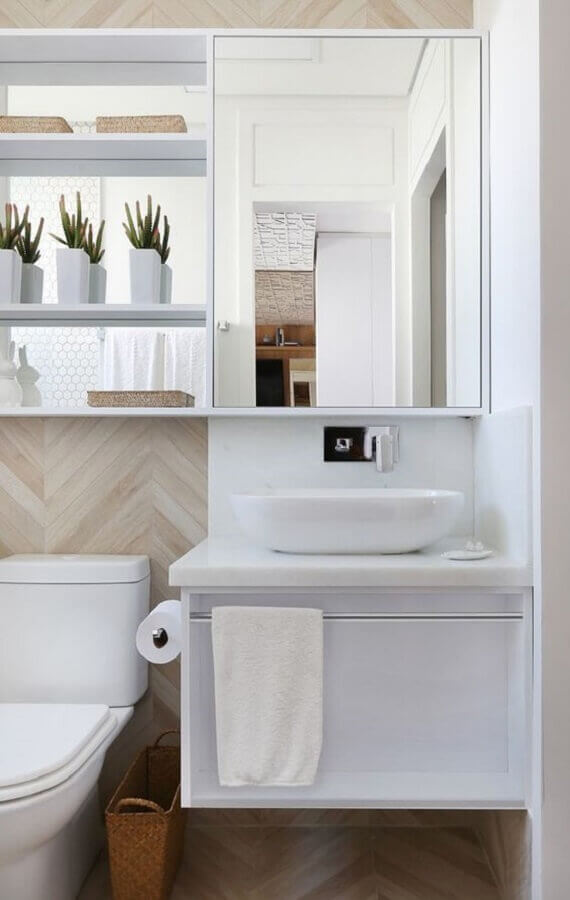 Decoração com revestimento na cor de madeira clara e gabinete para banheiro com espelheira