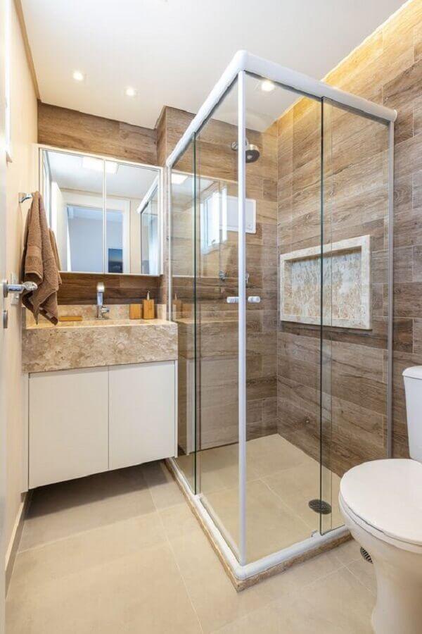 Decoração com revestimento que imita madeira e armário de banheiro planejado pequeno