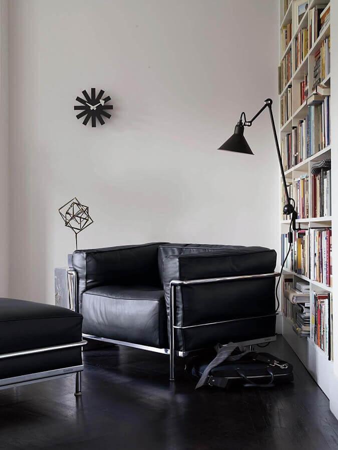 Decoração de cantinho de leitura com poltrona preta confortável