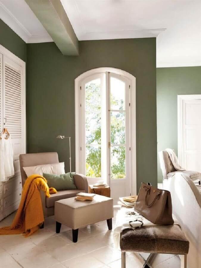 decoração de casa com parede verde oliva e poltrona bege Foto El Mueble