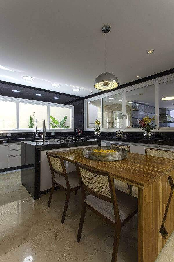 decoração de cozinha com ilha gourmet pequena integrada com mesa de madeira  Foto Iara Kilaris