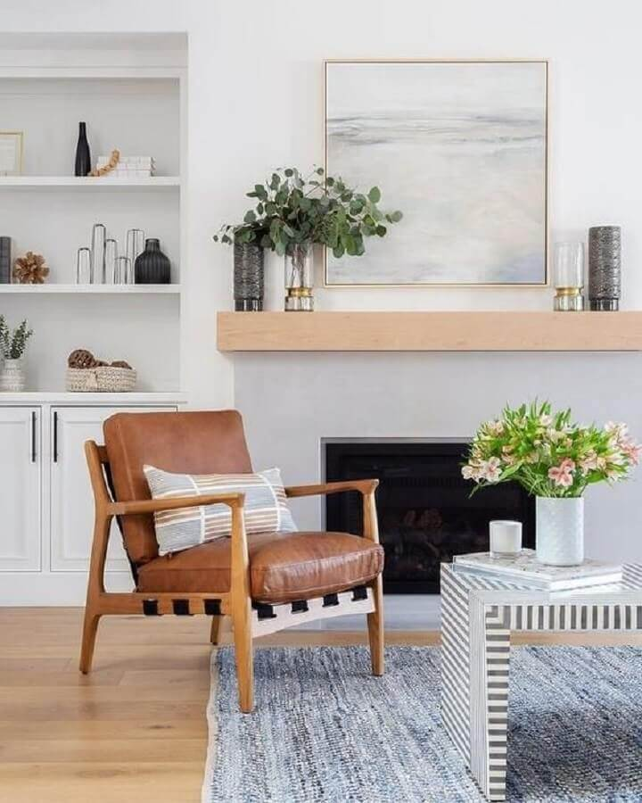 decoração de sala branca com poltrona marrom de madeira e lareira Foto Histórias de Casa