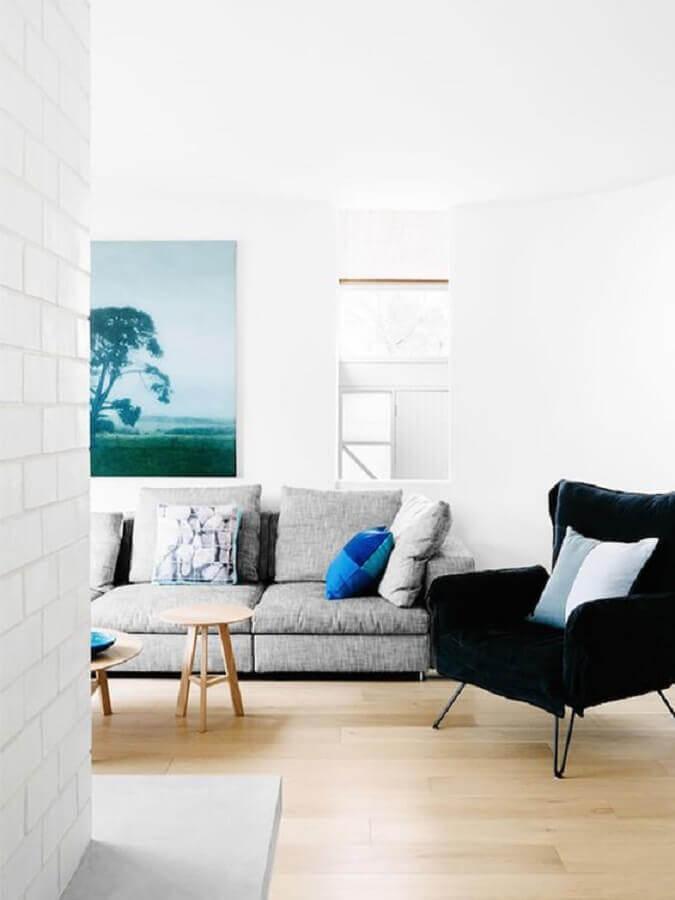 Decoração de sala branca com sofá cinza e poltroan preta confortável
