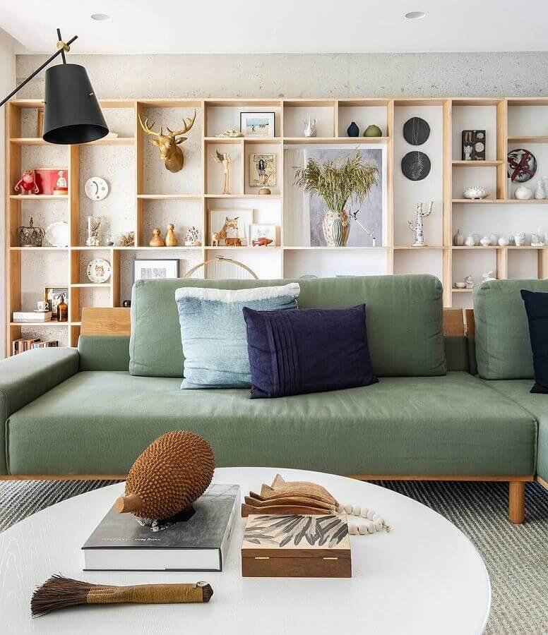 decoração de sala com sofá verde oliva e estante de madeira de nichos  Foto Fernando Jaeger