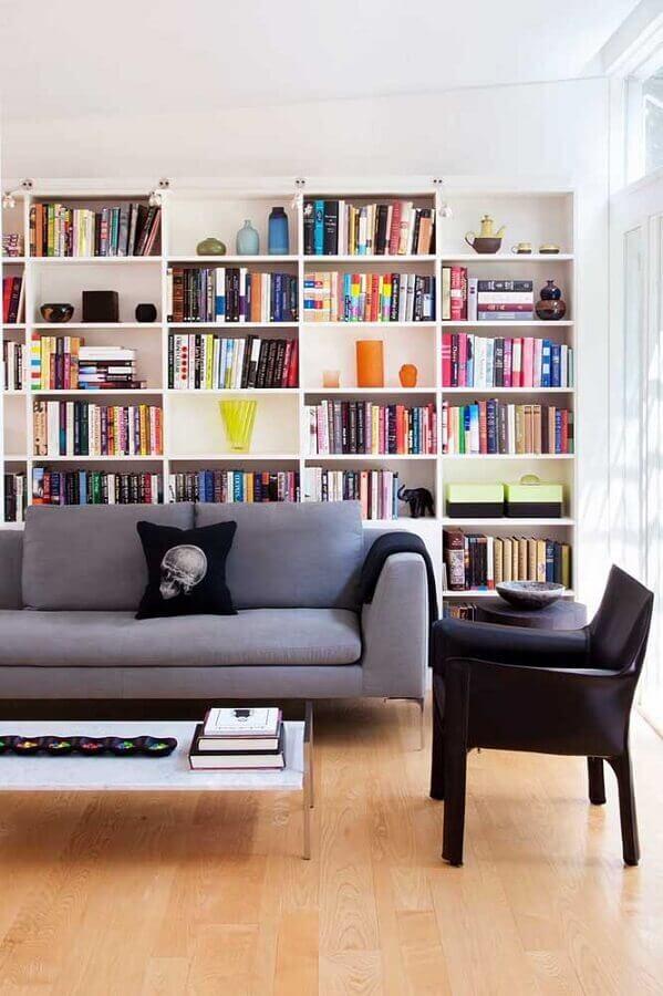 Decoração de sala de estar com estante de livros e poltrona preta pequena