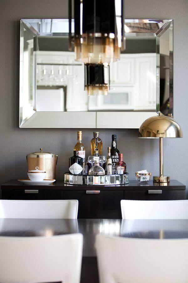 Decoração de sala de jantar com espelho e aparador de madeira
