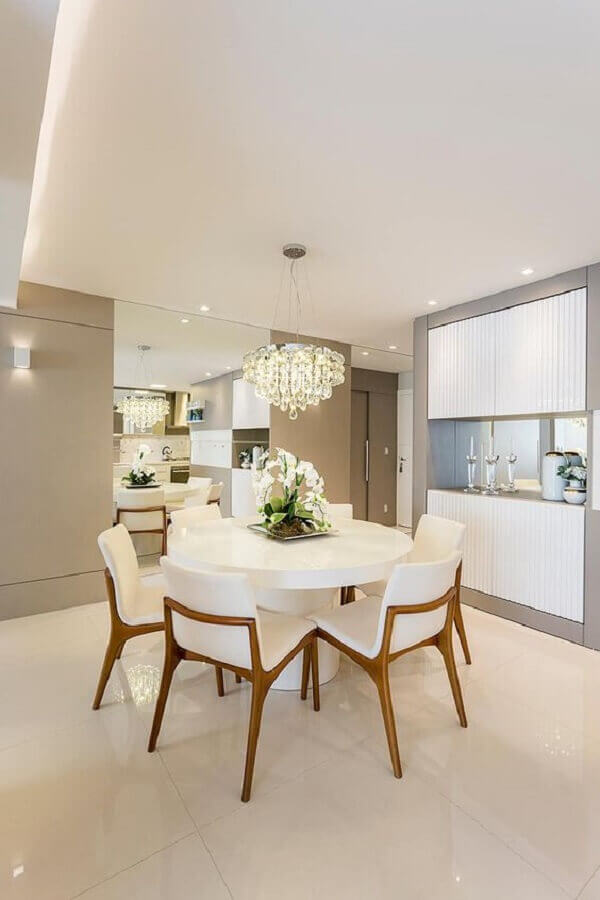 decoração de sala de jantar com lustre de crista e cadeiras acolchoadas para mesa redonda  Foto Homify