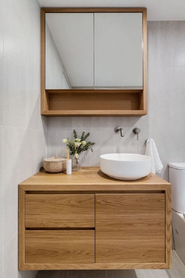 Decoração em cinza claro e madeira com armário de banheiro pequeno com cuba
