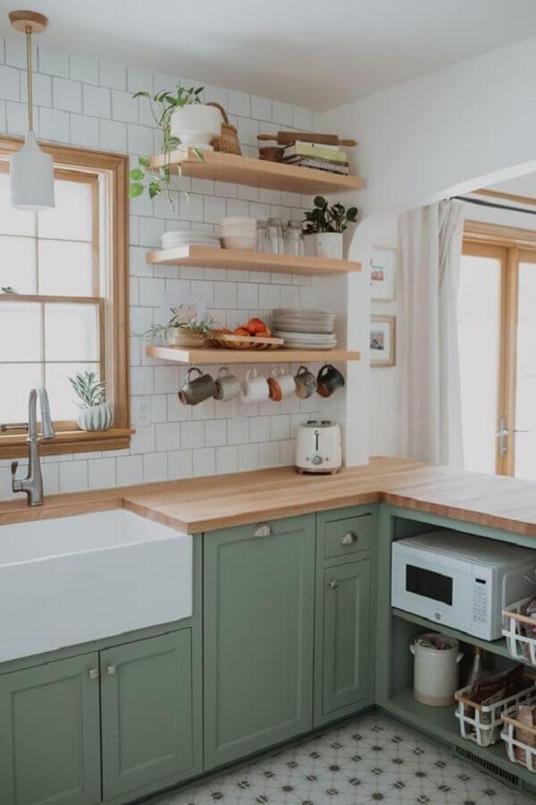 Decoração estilo retrô com bancada de madeira para armário verde e azulejo de cozinha branco