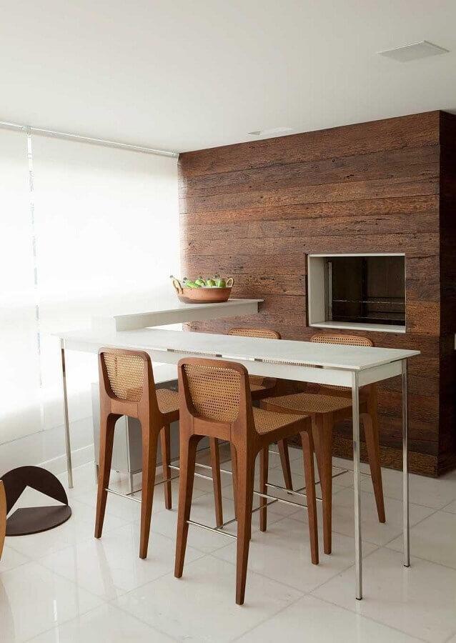 Decoração minimalista com banquetas para bancada de madeira em varanda gourmet com churrasqueira