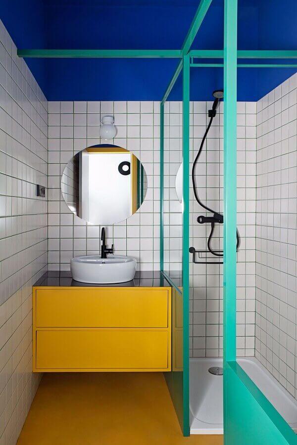 Decoração moderna para banheiro pequeno com gabinete amarelo e box cor verde água