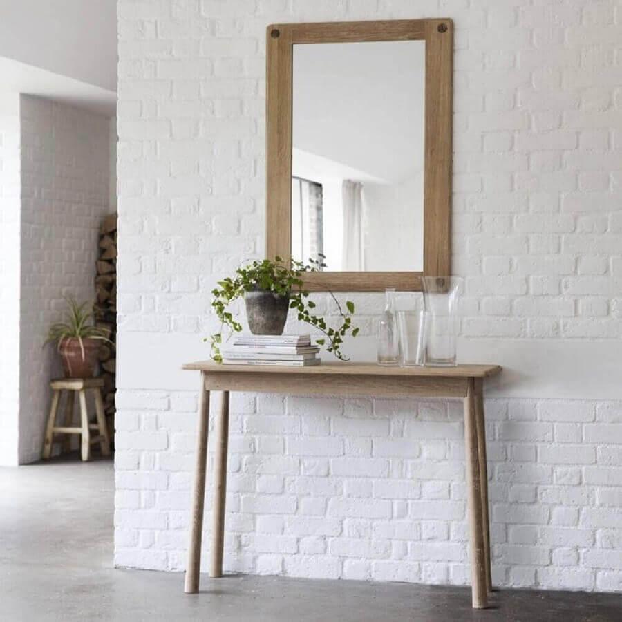 Decoração simples com aparador com espelho para corredor com parede de tijolinho branco