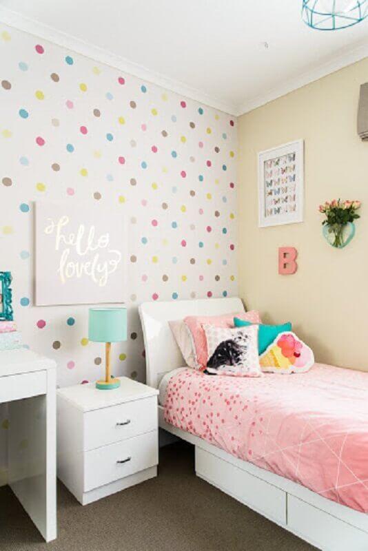 Decoração simples com papel de parede de bolinhas coloridas e almofadas para quarto infantil