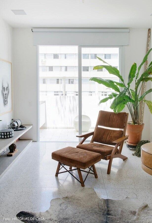 decoração simples para sala branca com poltrona marrom com puff  Foto Histórias de Casa