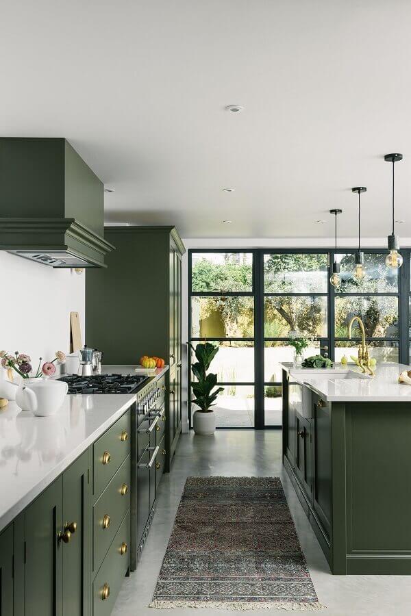 Decoração sofisticada para cozinha planejada com ilha e armários na cor verde escuro