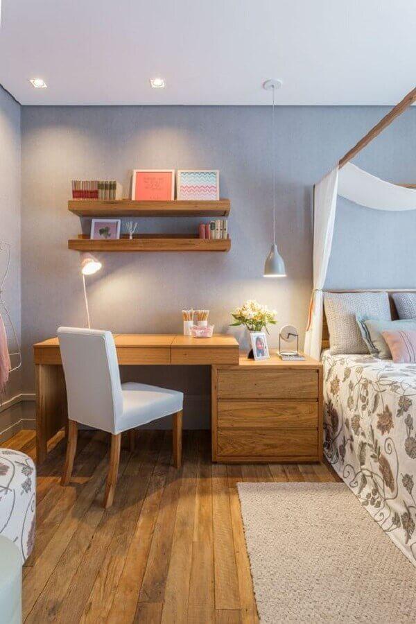Escrivaninha de madeira para home office no quarto de casal decorado com dossel