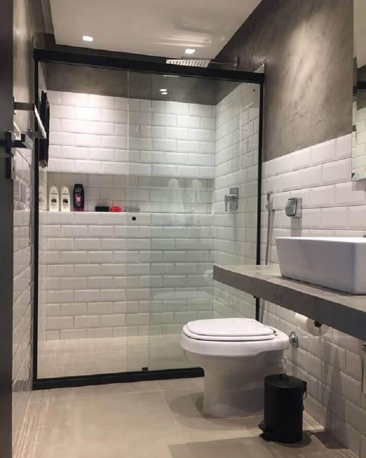 Parede de cimento queimado e azulejo de banheiro branco decoram o espaço