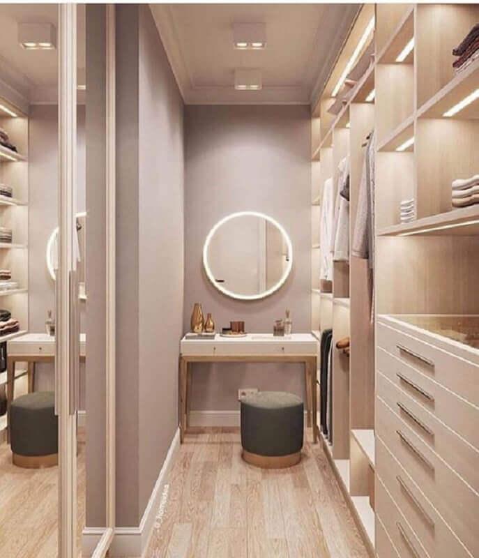 Guarda roupa closet pequeno sofisticado decorado em cores neutras com espelho redondo