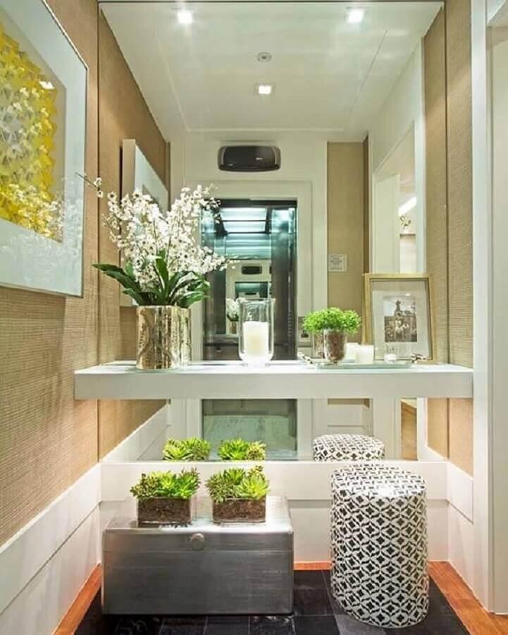 Hall decorado com parede espelhada e aparador branco suspenso