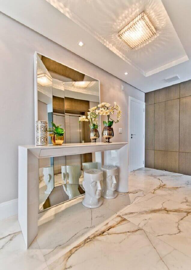 Hall sofisticado decorado com aparador branco e espelho grande