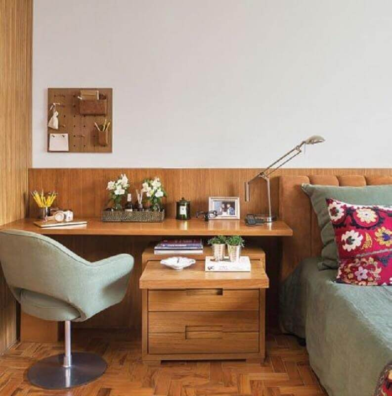 Home office no quarto de casal decorado com escrivaninha de madeira