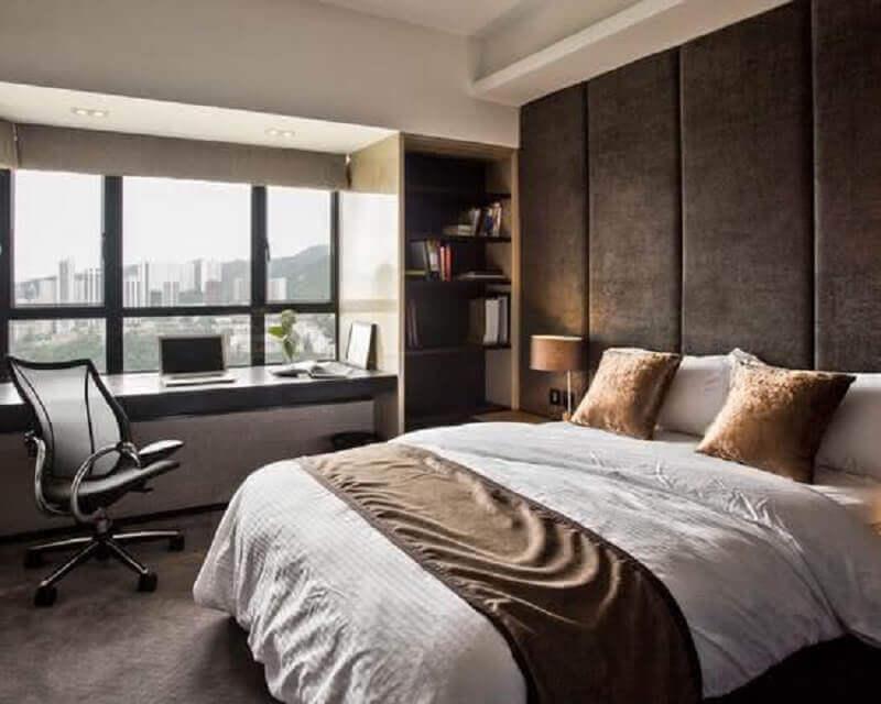 Home office no quarto de casal decorado com parede com cabeceira estofada