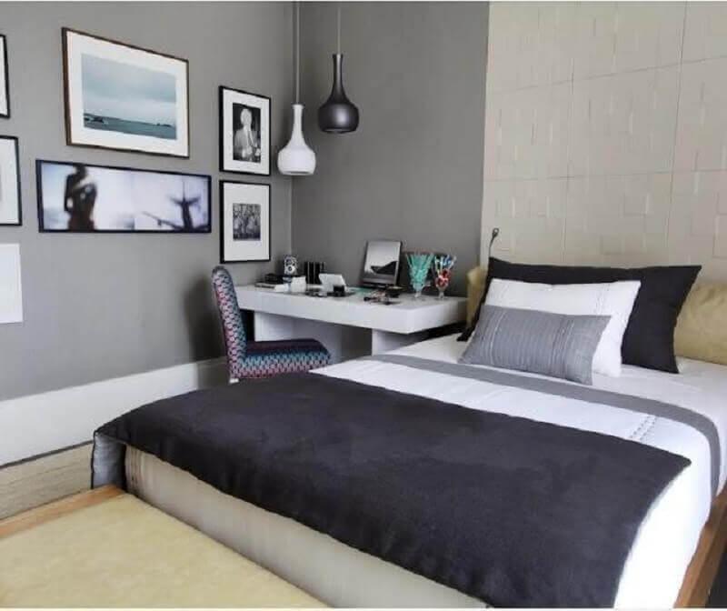 Home office no quarto de casal decorado em tons de cinza com escrivaninha branca