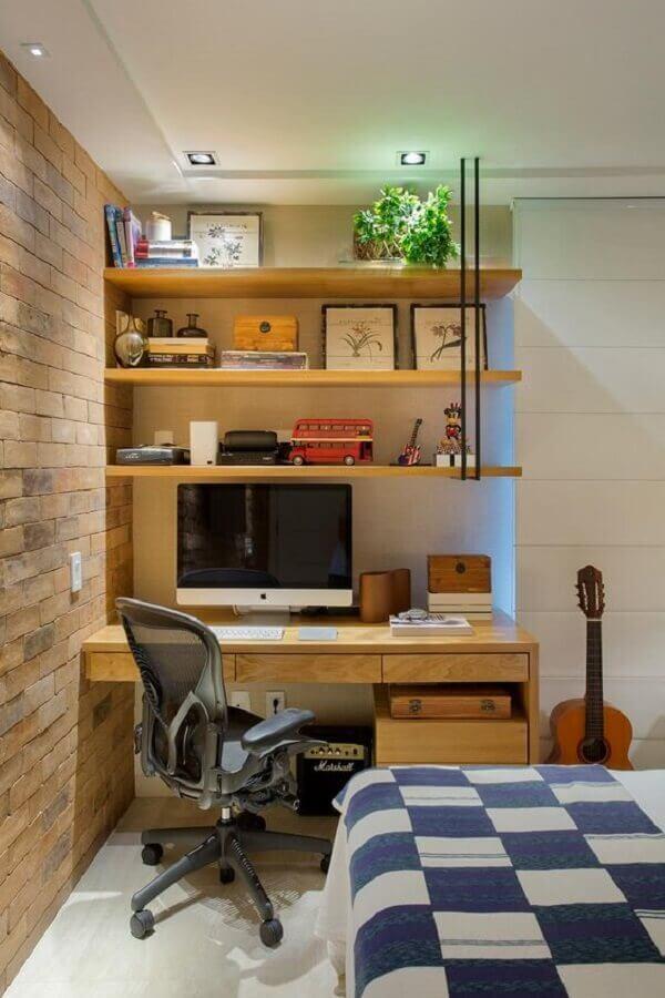 Home office no quarto decorado com parede de tijolinho e escrivaninha de madeira