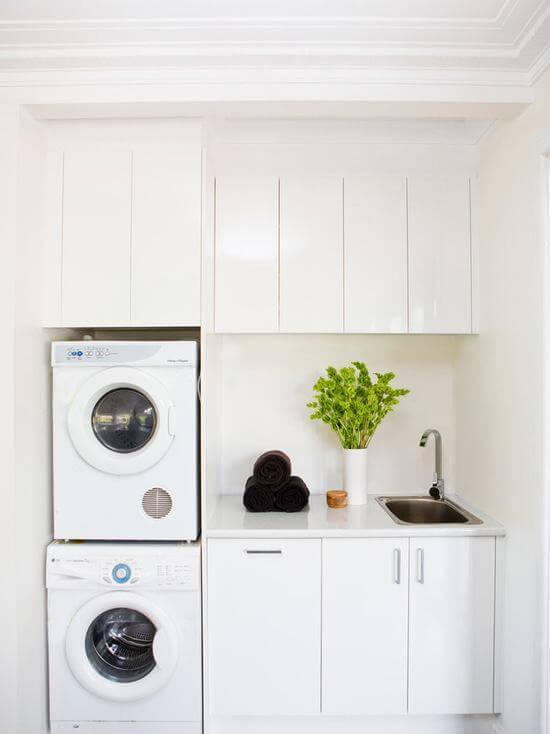 Lavanderia simples com armários planejados e brancos