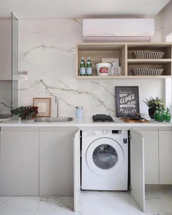 Lavanderia simples escondida nos armários da área gourmet