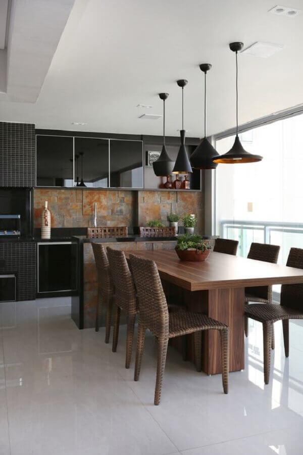 Luminária pendente para área gourmet preta decorada com mesa de madeira