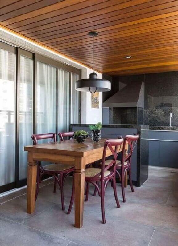 Lustre pendente para área gourmet decorada em cores escuras com mesa de madeira