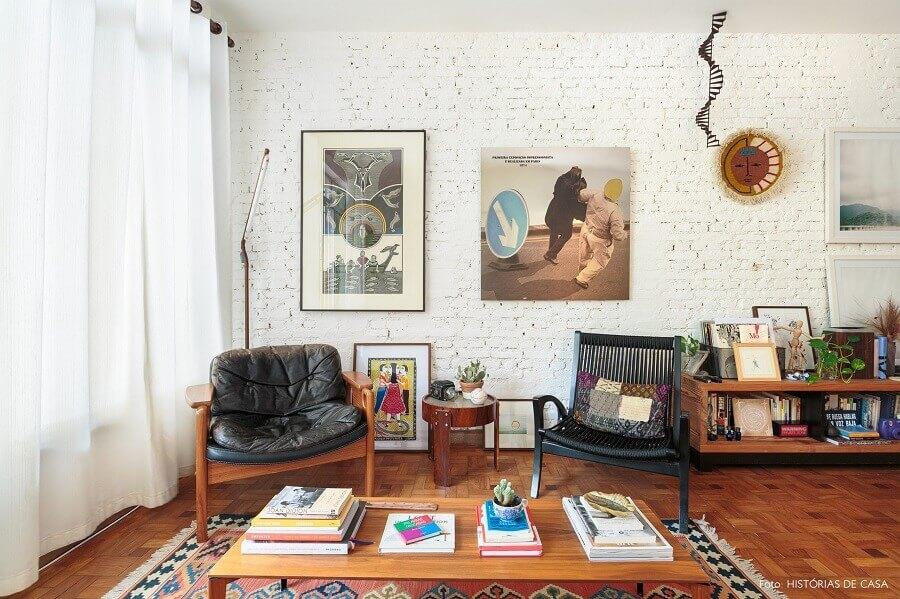 Modelos diferentes de poltrona decorativa preta para sala com parede de tijolinho branca