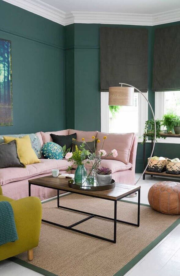 Parede na cor verde escuro para sala decorada com sofá rosa e luminária de chão