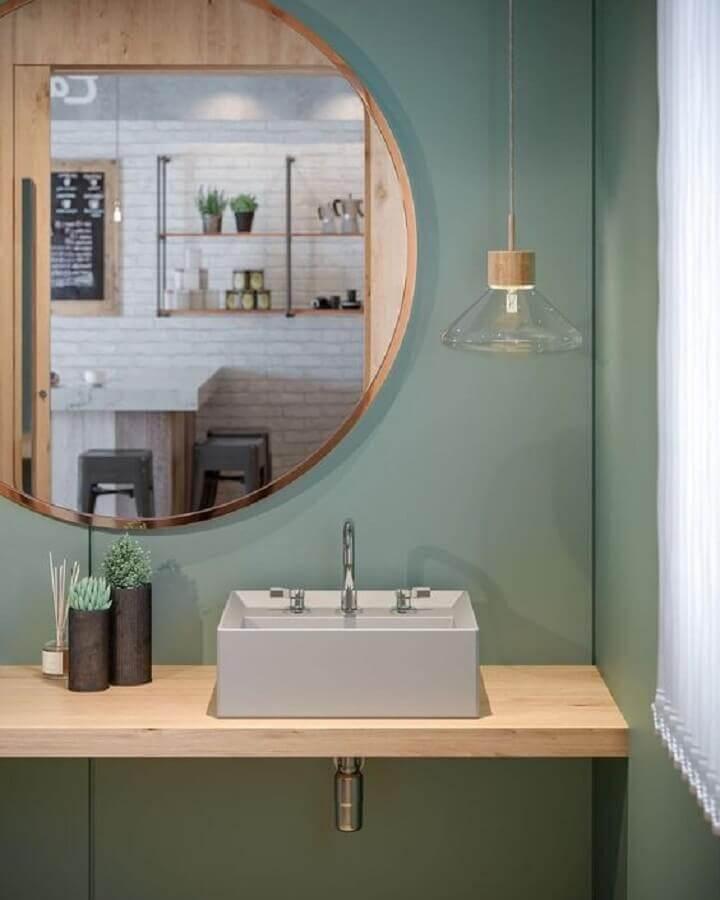 parede verde oliva para banheiro decorado com bancada de madeira e espelho redondo  Foto Archilovers
