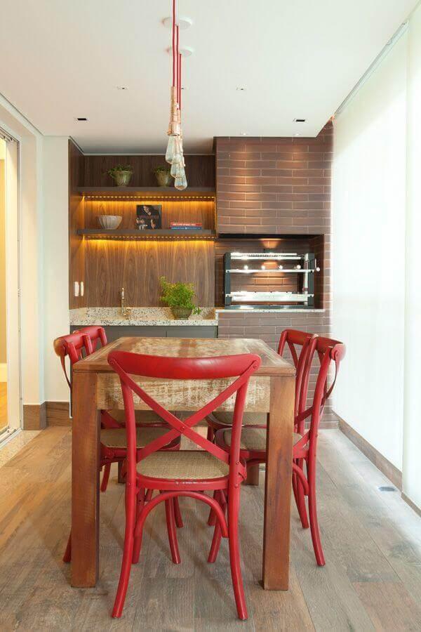 Pendente para área gourmet com churrasqueira decorada com cadeiras vermelhas para mesa de madeira
