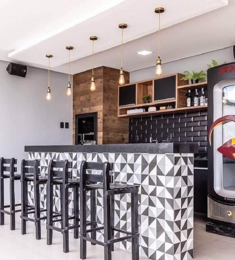 Pendente para área gourmet decorada com banquetas pretas e revestimento geométrico