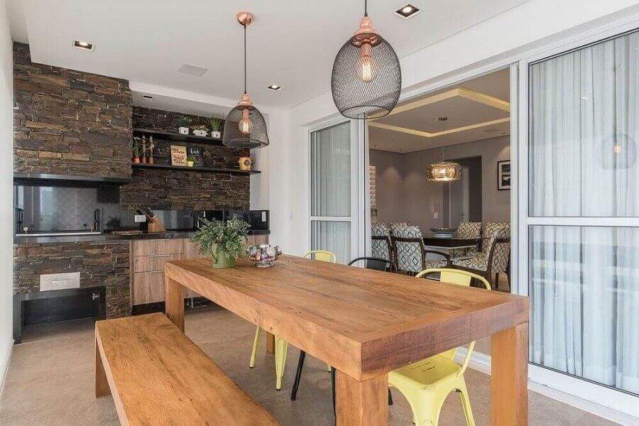 Pendente para área gourmet rústica e moderna decorada com revestimento de pedra e mesa de madeira