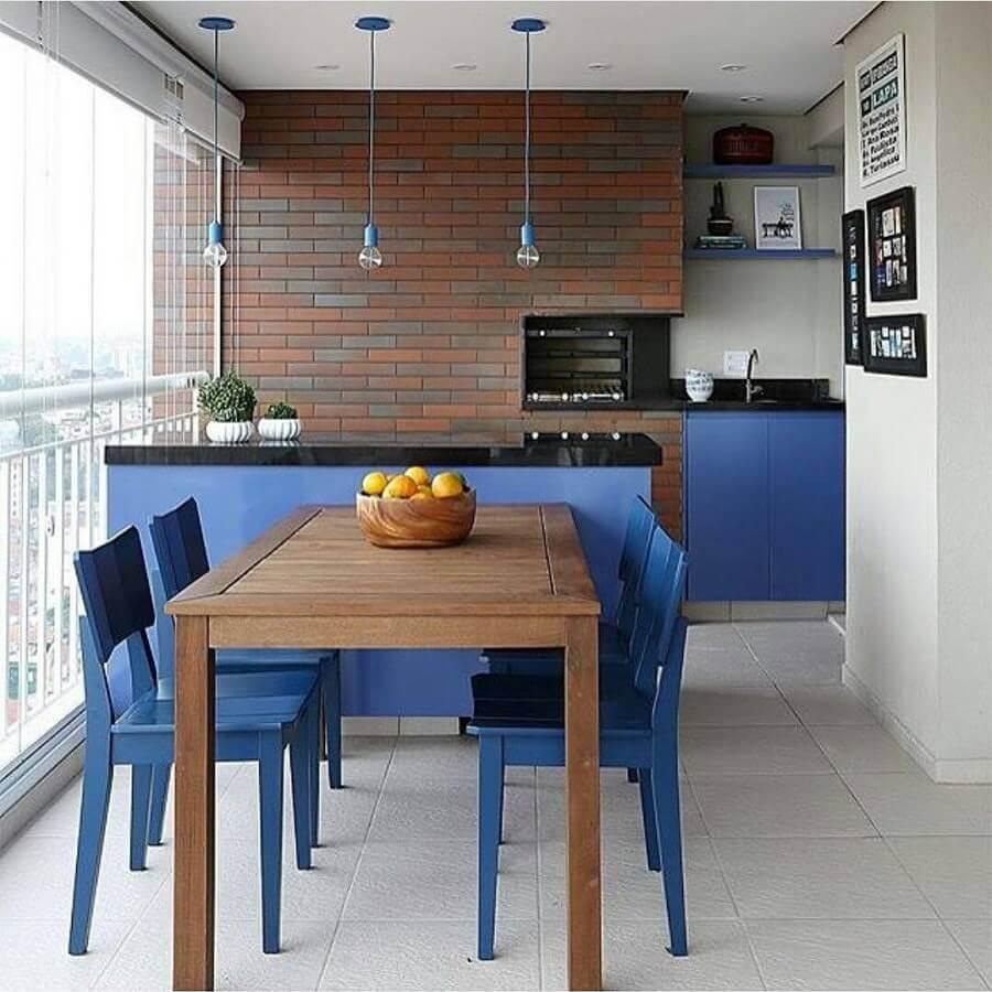 Pendente para balcão de área gourmet azul decorada com parede tijolinho e mesa de madeira