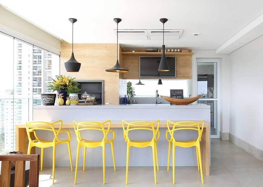 Pendente para balcão de área gourmet clean decorada com banquetas amarelas e revestimento amadeirado
