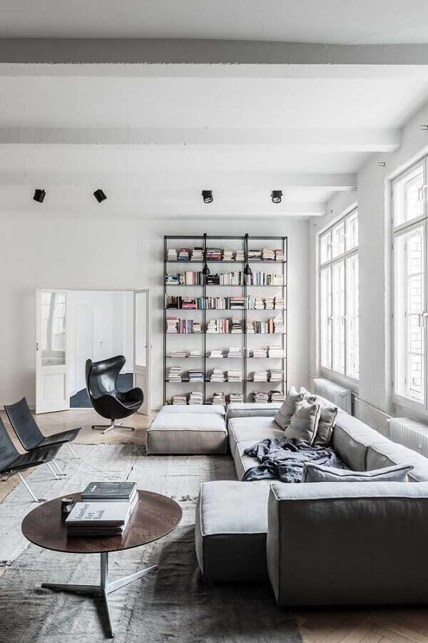 Poltrona giratória preta para sala decorada com sofá modular e estante de livros