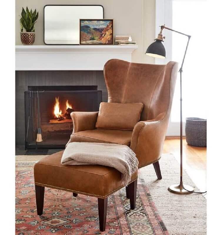 poltrona marrom com puff para decoração de sala de estar com lareira Foto Pottery Barn